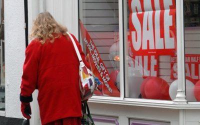 A woman walking past a shop