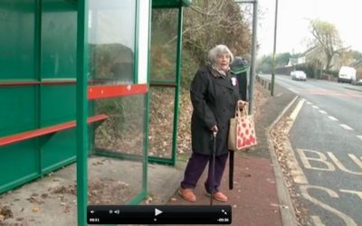An older lady at a bus stop
