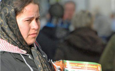 A woman selling a magazine