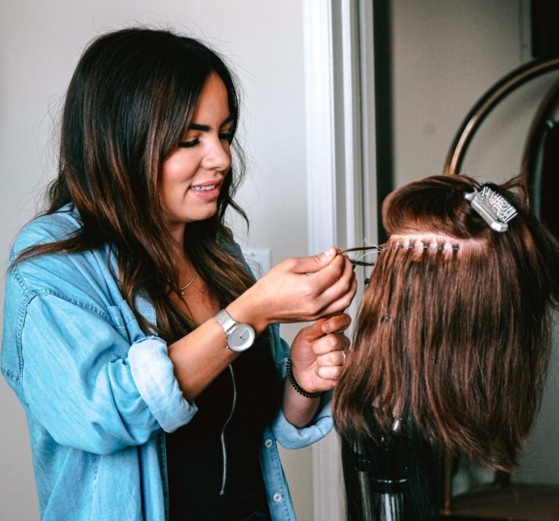 hairdresser styling a wig