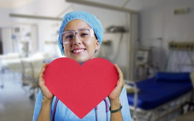 A smiling nurse holding a paper heart