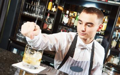 A bar tender prepares a drink