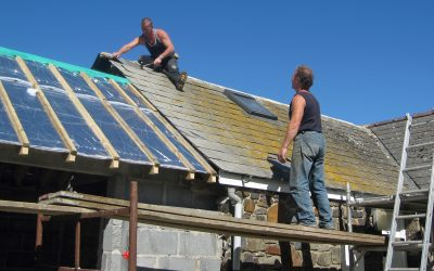 Two men fixing a roof