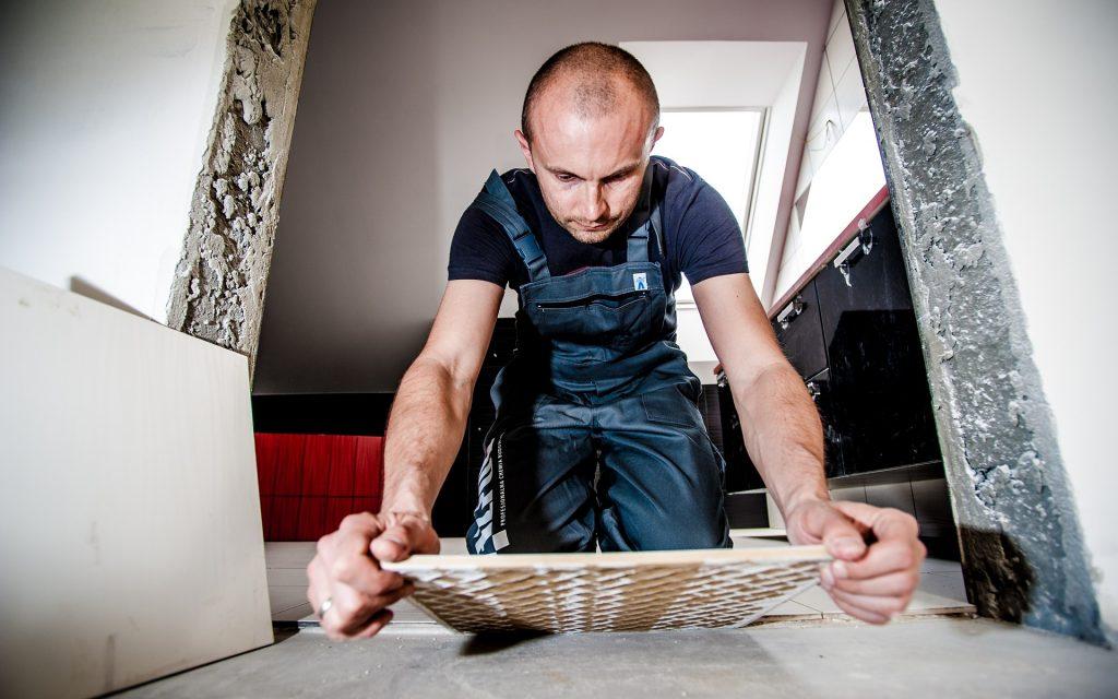 A man tiling a floor