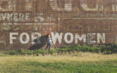 A child next to a wall saying for women