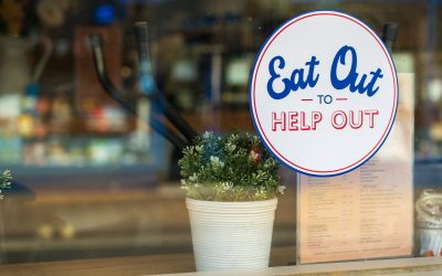A sign in a window saying eat out to help out